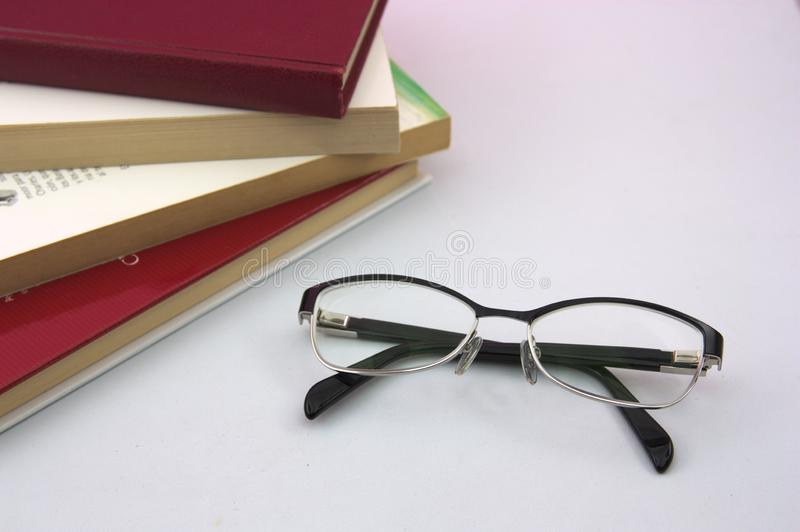 On a table we have some books and glasses to read up close. On a white table we have some books of different colors and next to them some reading glasses royalty free stock photo
