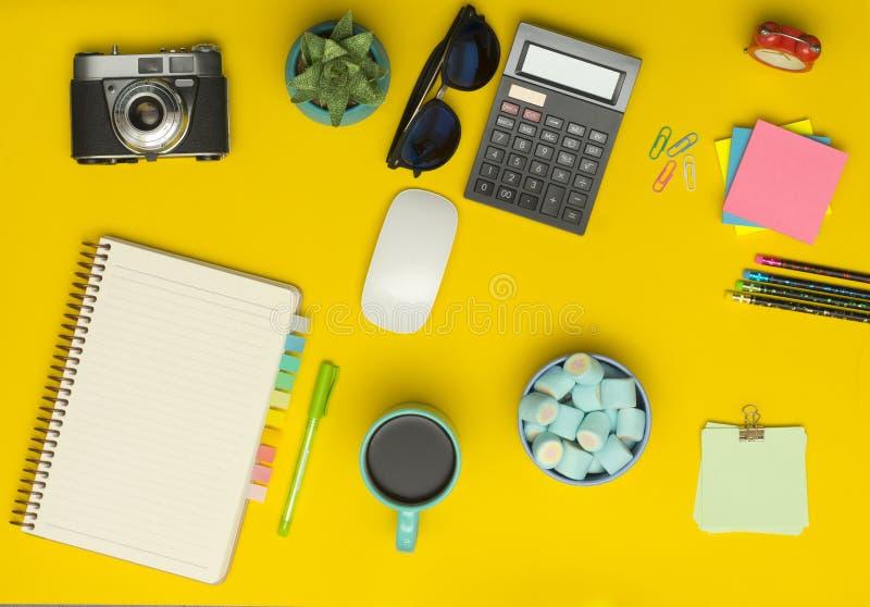 Table jaune de bureau avec l'appareil-photo, carnet, calculatrice, tasse de café images libres de droits