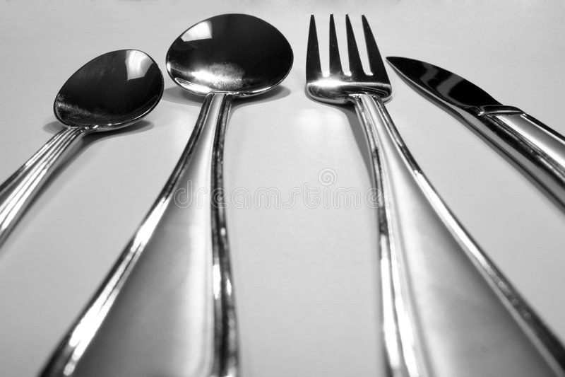 The table knife, fork, spoon. On gray royalty free stock photo