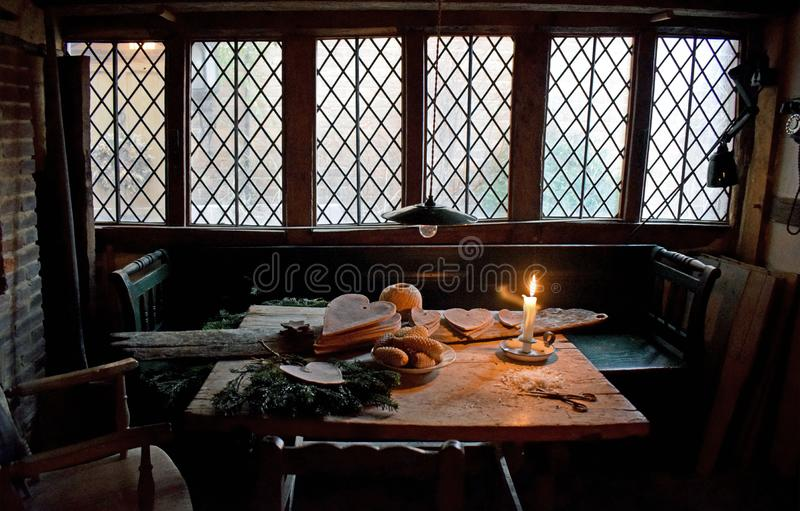 A photo of the tudor era. A table laid for a meal set in the Tudor era for at Christmas time with bread cutlery and a candle for lighting in front of a large old royalty free stock photo