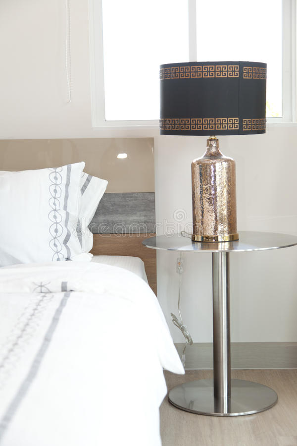 Table lamp in bedroom. Black table lamp in bedroom royalty free stock photo