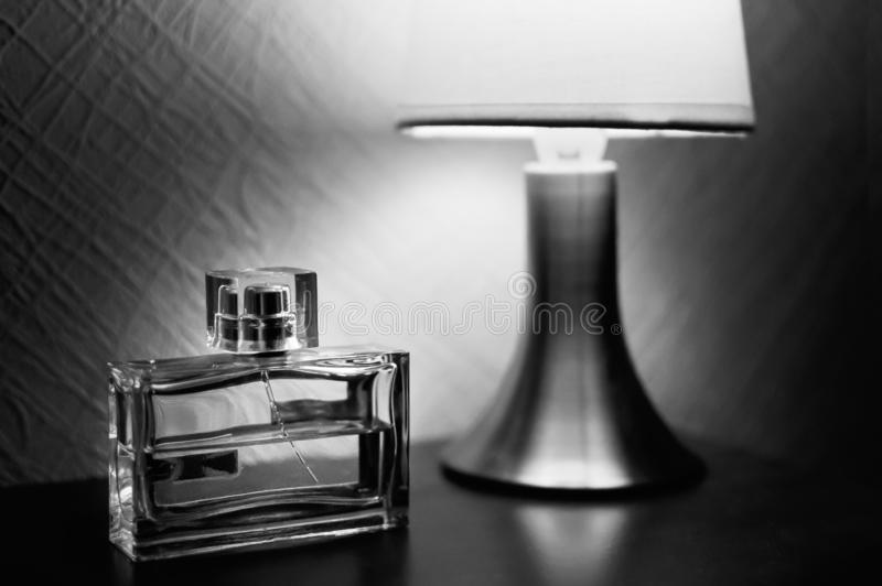 Table lamp with shade burlap burning on a wooden table and a bottle of men`s fragrances. Black-and-white picture royalty free stock images
