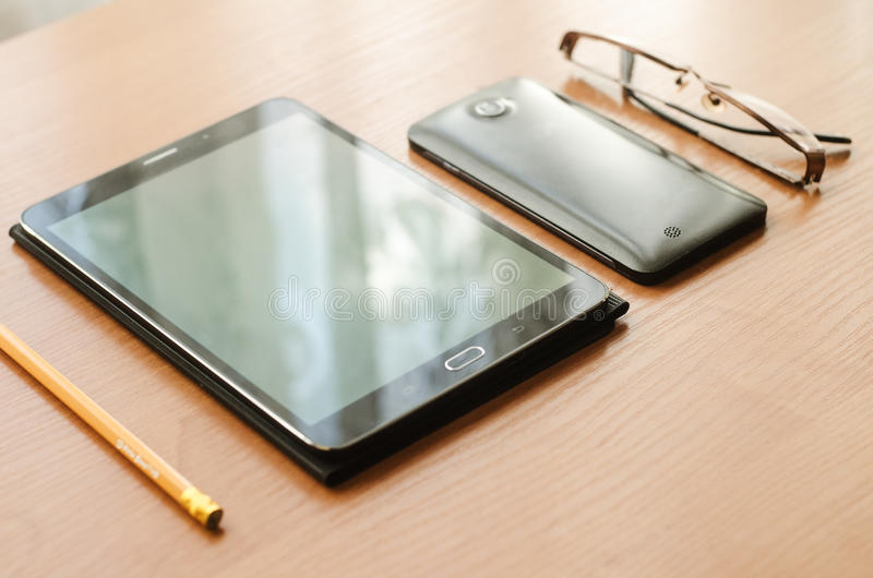 On table lay glasses and a tablet, a smartphone and a pencil stock image