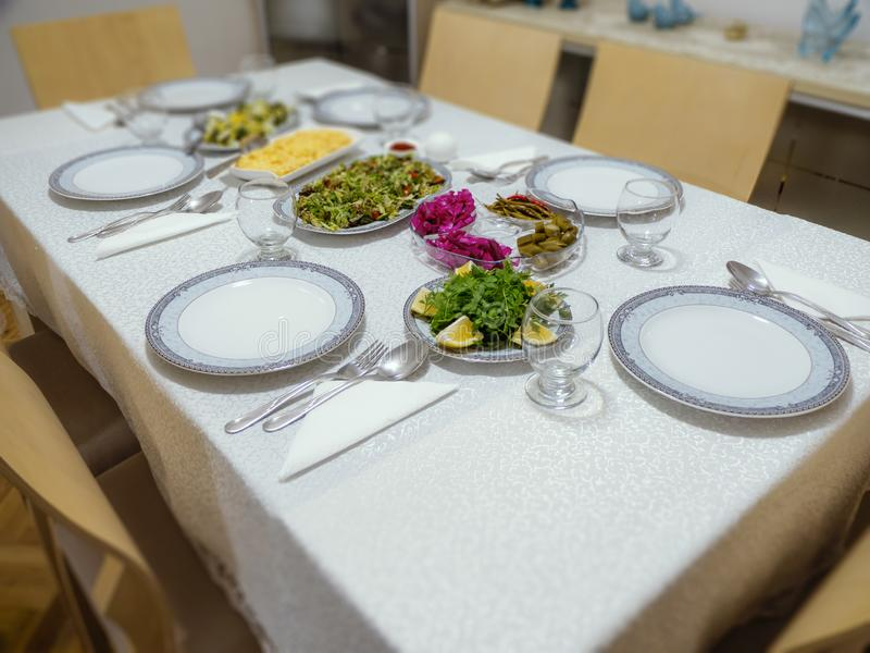 Table layout prepared for dinner in turkish family house. plate, fork-spoon and salad dishes on the dining table royalty free stock photography