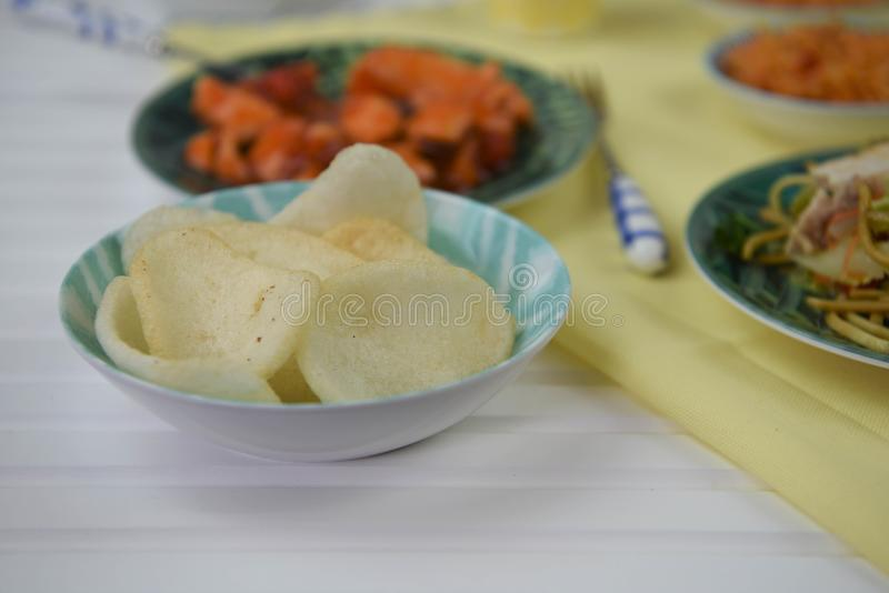 Prawn crackers served on a table with traditional Chinese dishes. A table layout with traditional Chinese food of fresh crisp crunchy prawn crackers in a dish royalty free stock photos