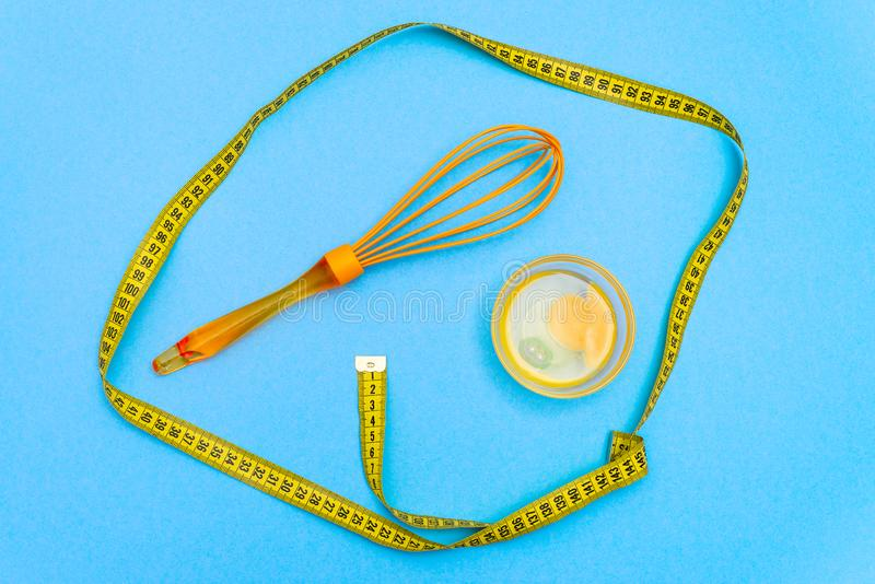 On the table lies a broken chicken egg in the plate, next to the whisk for whipping. Protein diet food. blue background stock photo