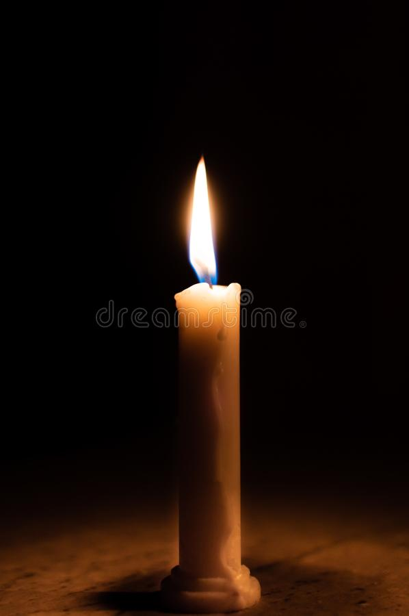 A table lit by a candle in a dark room royalty free stock photos