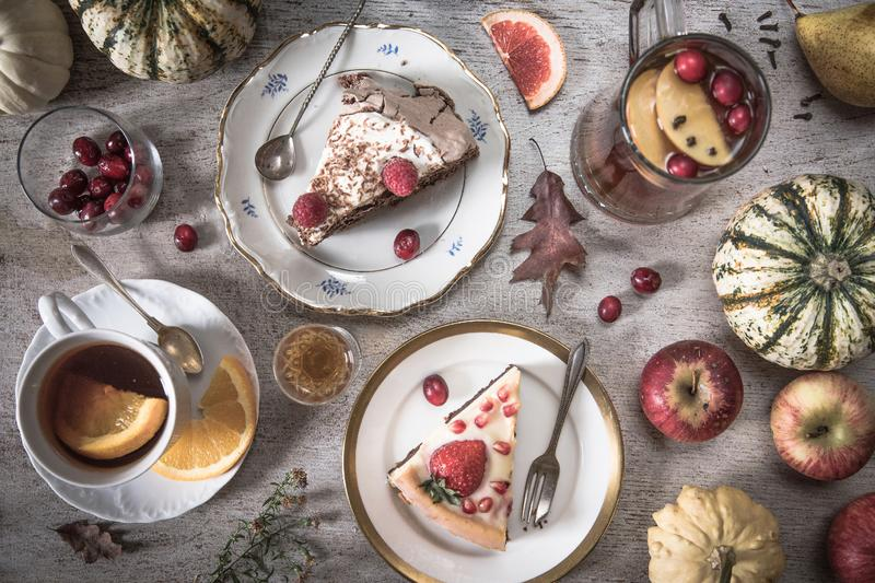 Table with loads of tea, cakes, cupcakes, desserts, fruits, flowers and Ancient spoons and a pear, apples and pumpkins. Vintage style stock image