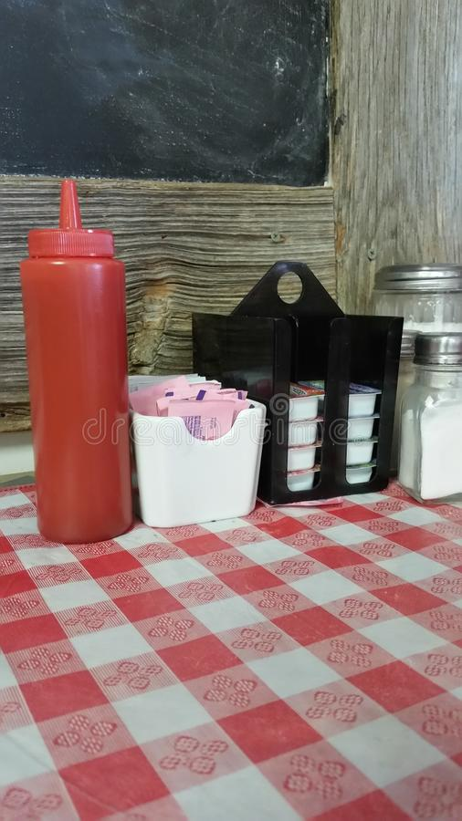 At The Diner Table, Lunch Time with Sweet Condiments. Table is set for lunch. Settings include salt, sugar, ketchup and sugar free sweetner stock photo