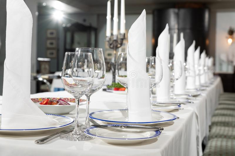 Table at a luxury wedding reception. Beautiful flowers on the table. Serving dishes, glass glasses, waiters work. Decoration, setting, banquet, event stock photo