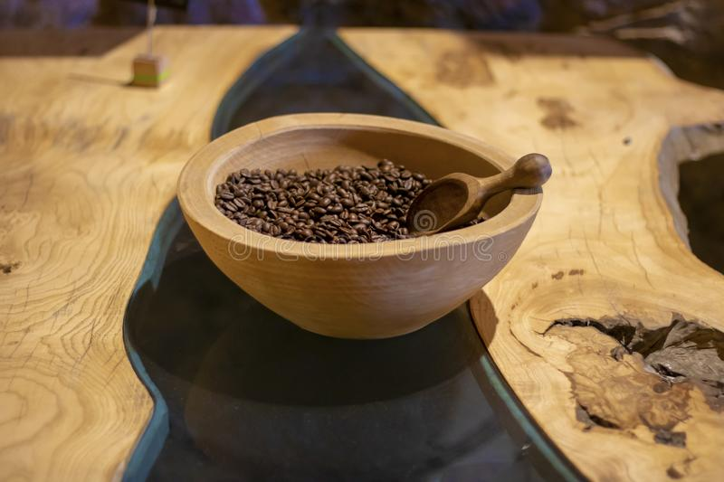 Table made of wood and glass. Coffee beans and spoon are in a wooden bowl stock image