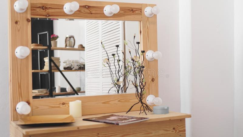 Table with makeup products and mirror near white wall. Dressing room interior stock photo
