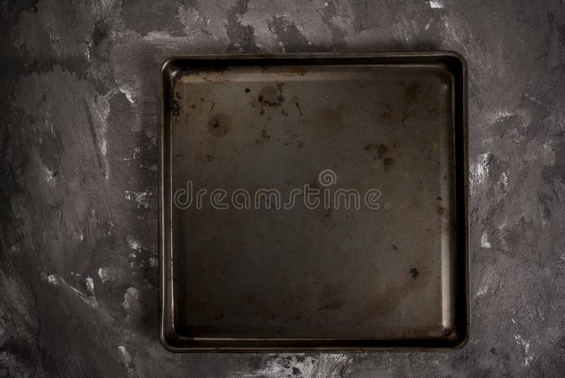 Table with metal baking tray. Grey black spotted stone concrete table with a metal baking tray, background, blank royalty free stock photos