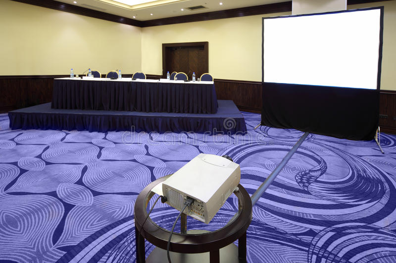 Table with microphone near screen. Big table with microphone near screen in bright conference hall, view from projector stock photos
