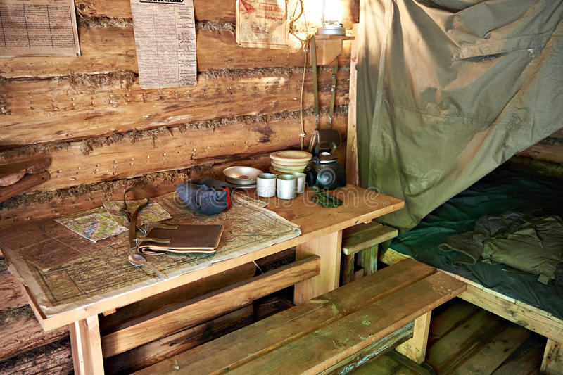 Table with military map, bed and utensils partisan dugout. Table with military map, bed and utensils in the partisan dugout royalty free stock photography