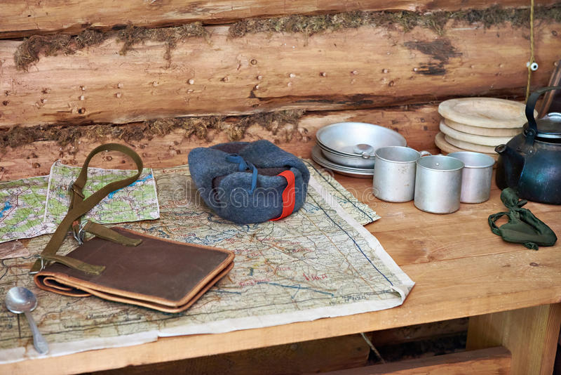 Table with military map, winter hat and utensils partisan dugout. Table with military map, winter hat with earflaps and utensils in the partisan dugout stock photography
