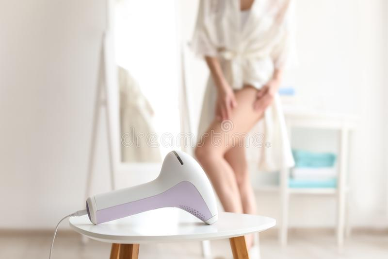 Table with modern laser epilator and young woman royalty free stock image
