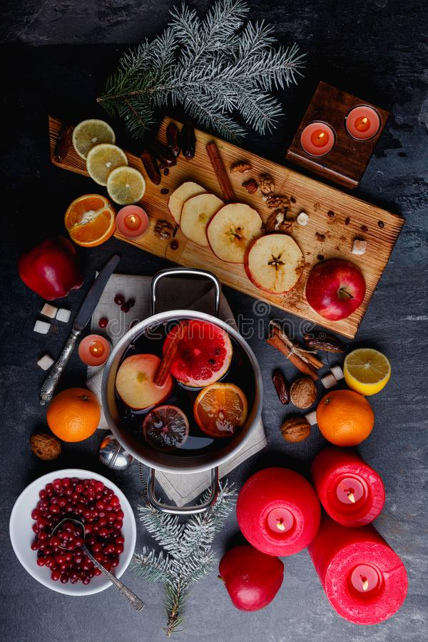 On the table is mulled wine, cranberries, a board with sliced fruit, candles and a sprig of Christmas trees. On the table is a metal pot with fragrant mulled royalty free stock image
