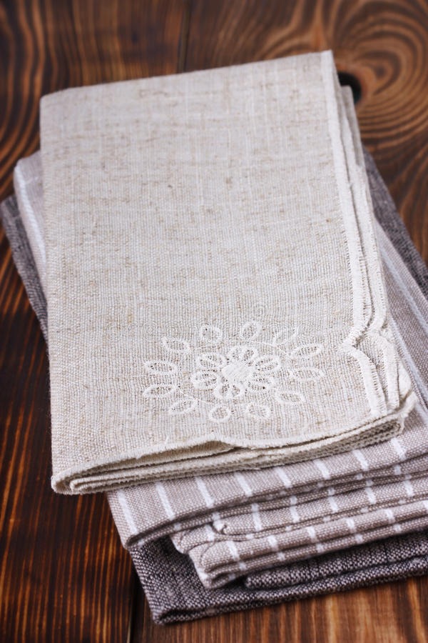 Table napkins. Pile of linen table napkins on a wooden background stock image