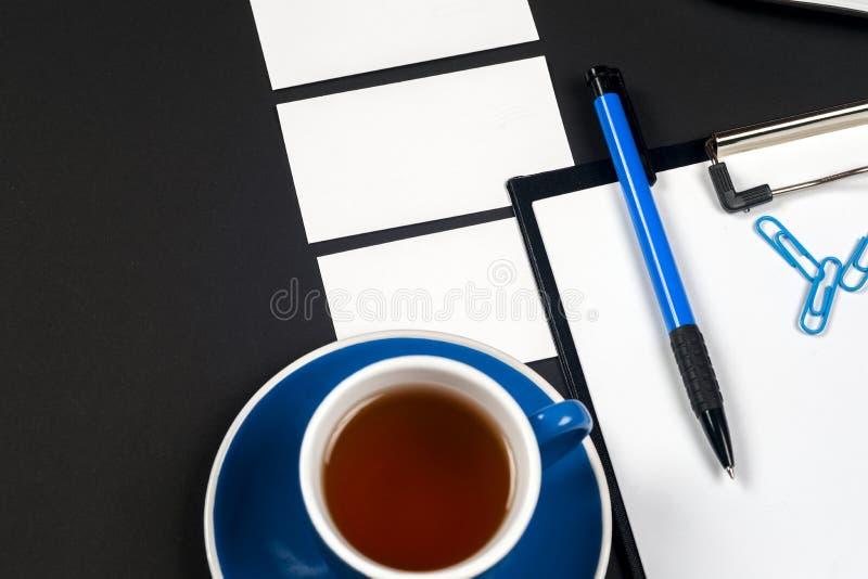 Table noire de bureau de bureau avec l'ordinateur, le blanc de carte de visite professionnelle de visite, la fleur, la tasse de c photo stock