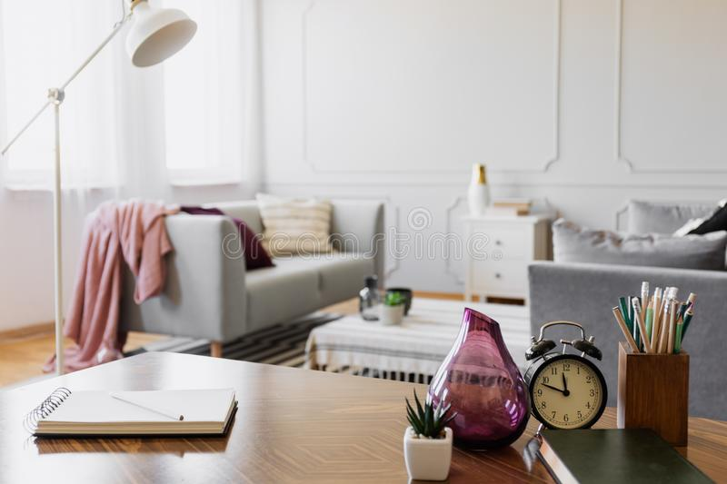 Table with notebook, small plant in pot, glass vase, clock and pencils in cup, real photo with copy space. Concepy stock photography