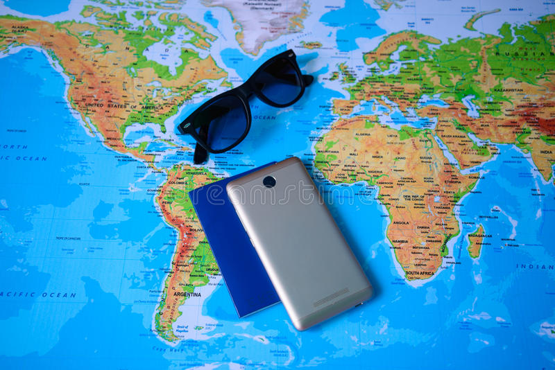 Table with open map showing plans for travelling and related items. Including camera passport smartphone sunglasses hat and journal stock images