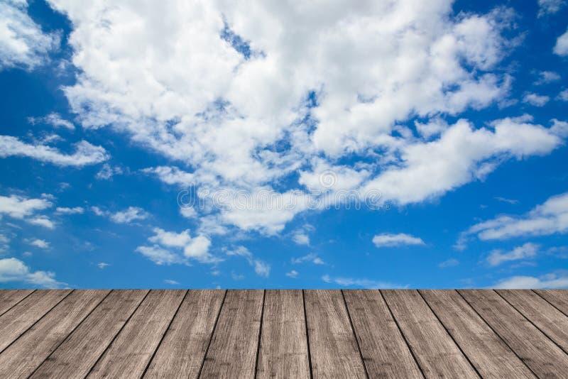 Table ou terrasse en bois sur le ciel bleu et les nuages profonds L'espace pour y image stock