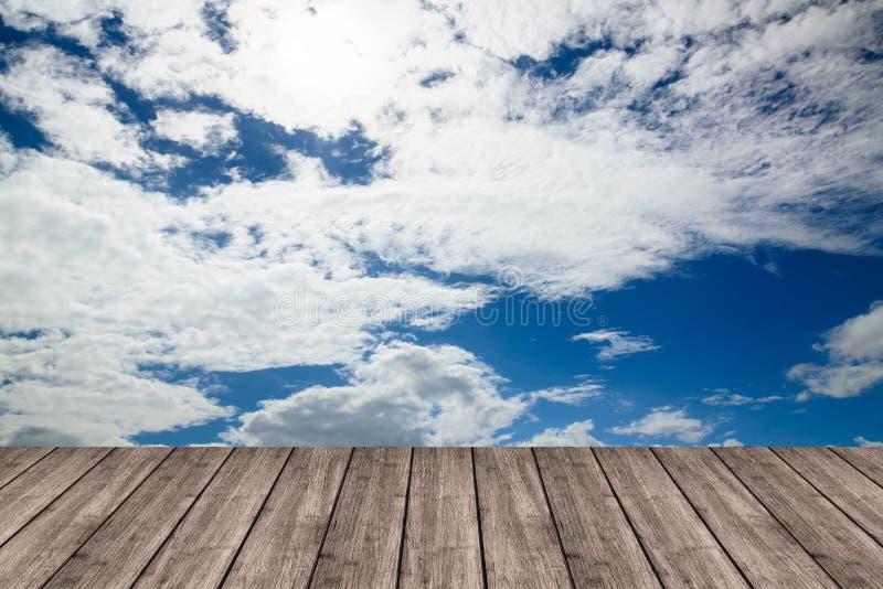 Table ou terrasse en bois sur le ciel bleu et les nuages profonds L'espace pour y photo stock