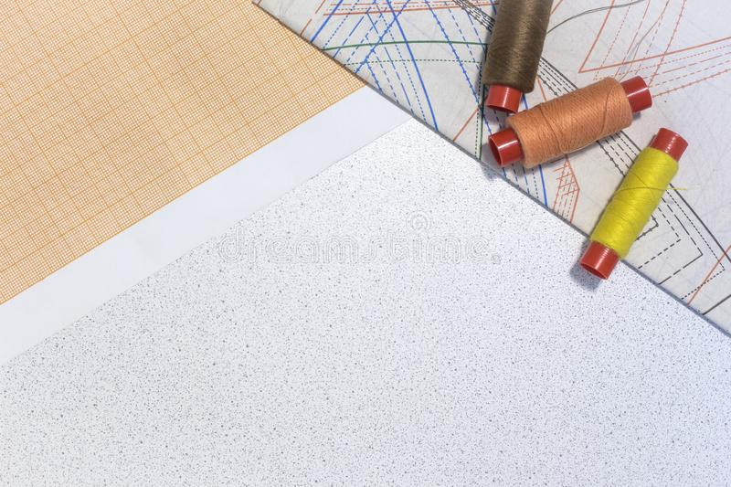 On the table paper with drawings of clothes, and sewing thread.copy space stock images