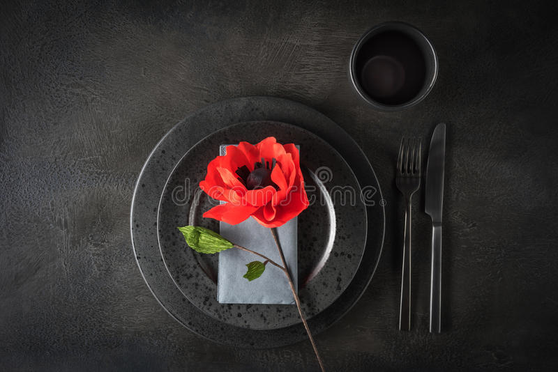 Table with paper flower. Dark and moody black and grey table decoration with paper flower stock photo