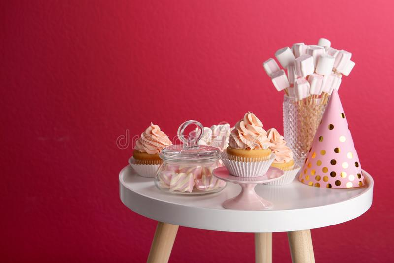 Table with party hat, cupcake and other sweets on burgundy background. Candy bar royalty free stock photos