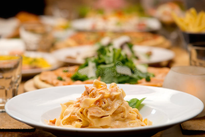 Table of pasta and other food plates royalty free stock photo