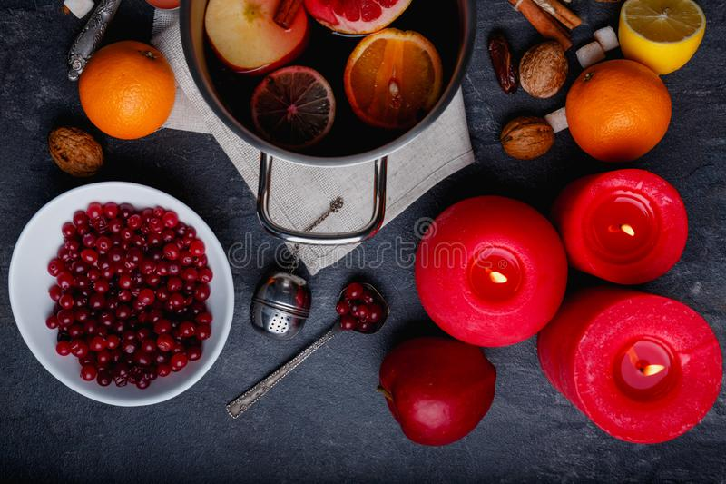 On the table is a pot of fragrant mulled wine, cranberries, apples and oranges and burning candles. View from above. On the table is a pot of fragrant mulled royalty free stock photography