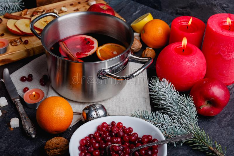 On the table is a pot of mulled wine, a plate with cranberries, oranges, apples and burning candles. Indoors. On the kitchen table is a pot of mulled wine, a royalty free stock images