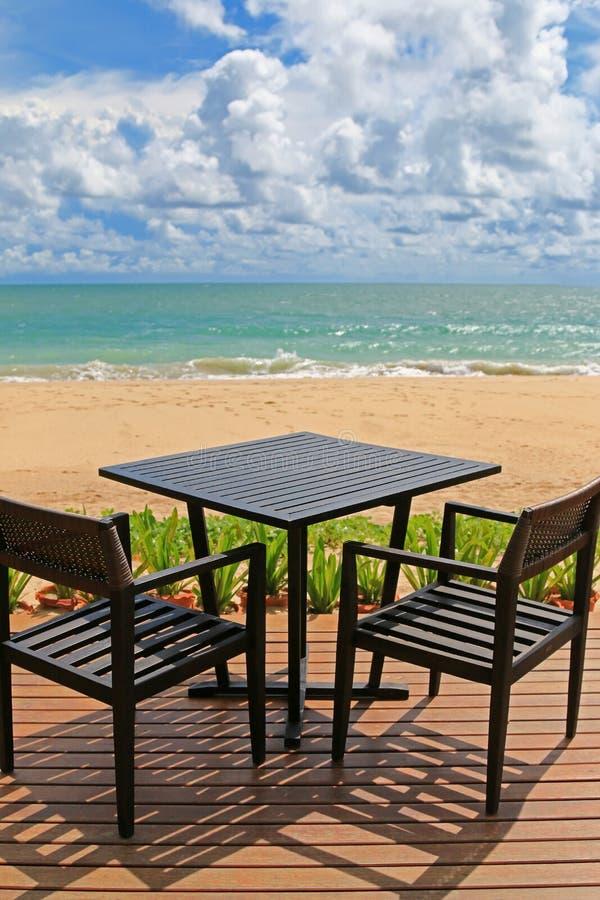 Table pour deux sur le balcon en bois avec la plage brouillée et bleu noirs photographie stock libre de droits