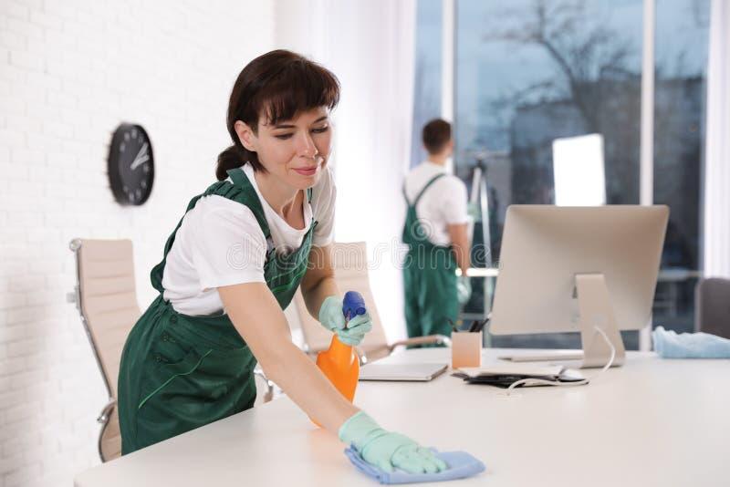 Table professionnelle de nettoyage de portier dans le bureau photographie stock