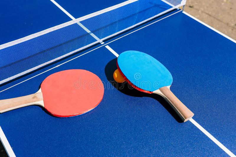 Table and rackets for playing table tennis or ping-pong. Blue table with white mesh and blue and red rackets. Orange ball. Table stock photography