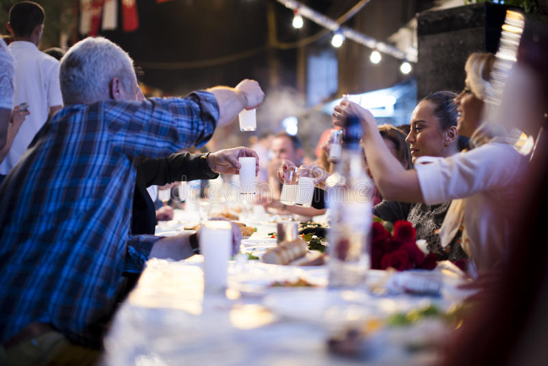 Table of raki. Izmir, Turkey - May 5, 2015: Hidirellez night. people having fun on the turkish raki table. Hidirellez is celebrated as day on which prophets stock photography