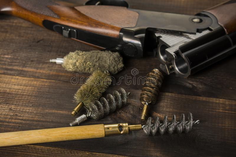 Cleaning the gun on a wooden table royalty free stock photo
