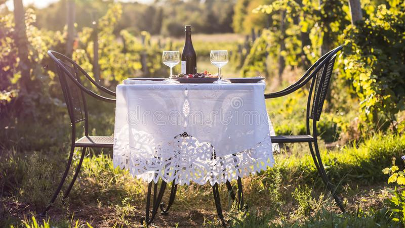 Table for a romantic dinner outdoors. Bottle of wine next to two empty glasses stock images