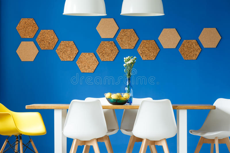 Table and royal blue wall. Royal blue wall in simple scandinavian dining room with wooden and white communal table, chairs and honeycomb cork wall decor royalty free stock photos