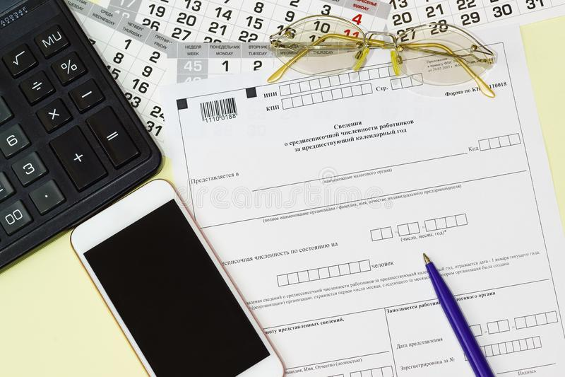 On the table is the Russian reporting form Information on the average number of employees for the previous calendar year. Accountant`s work stock image