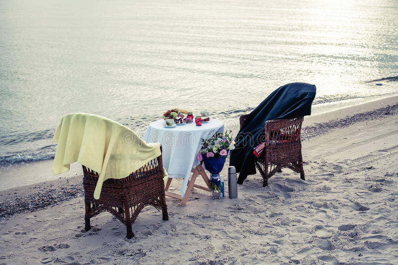 Table on seacoast. Table and chairs on seacoast for a romantic meeting royalty free stock image