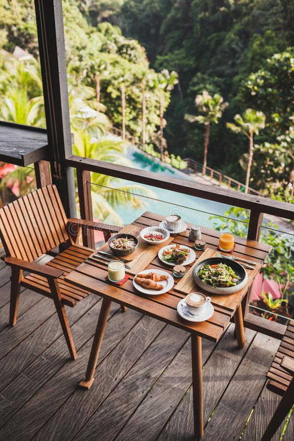 Table with served breakfast on wooden terrace. With pool and jungle view in Bali stock images