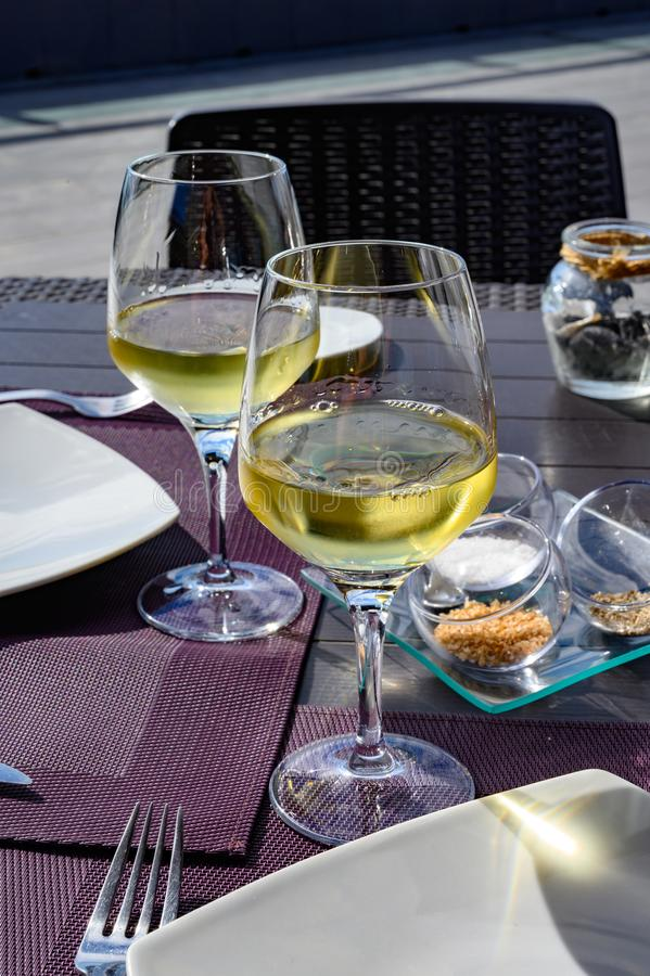 Table served for dinner on outside terrace with glasses of cold white wine and sea view stock photos