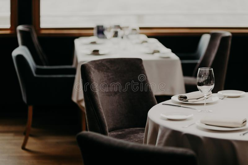 Table served for luxury dinner party with napkins, glasses and plates on white tableclothes. Nice decor. Wedding Banquet. Cozy atm. Osphere in restaurant royalty free stock photo