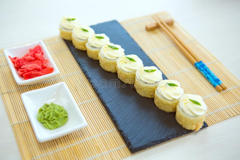 Table served with sushi and traditional japanese food on a dark background. Sushi rolls, hiyashi wakame, miso soup, ramen, fried royalty free stock image