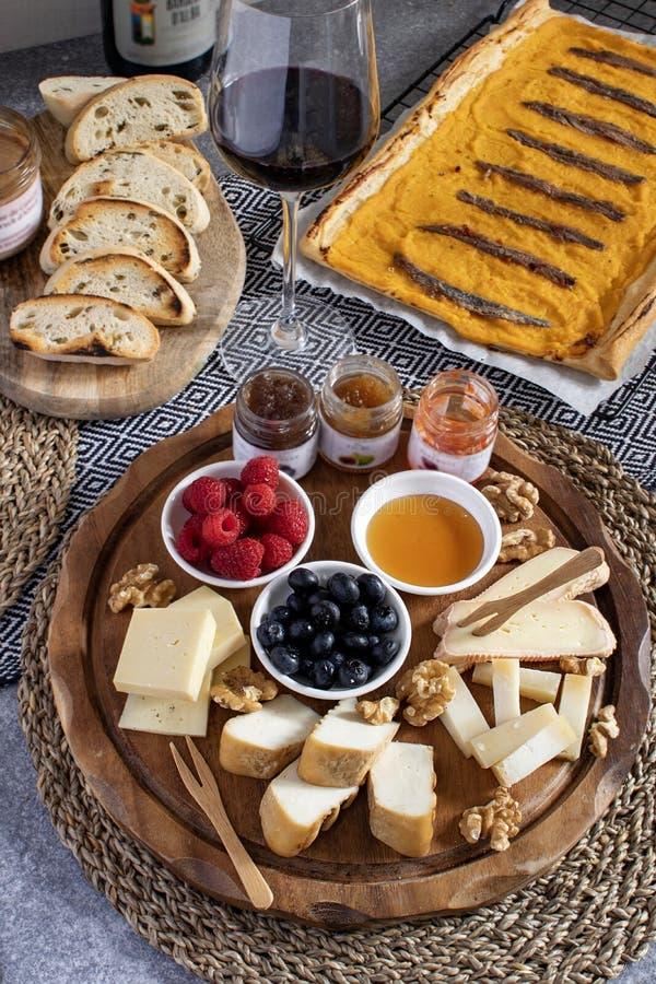 Table servie - apéritif de vin, assortiment de fromage sur le panneau en bois rond, noix, baies, miel, confitures, pain, vin roug images stock