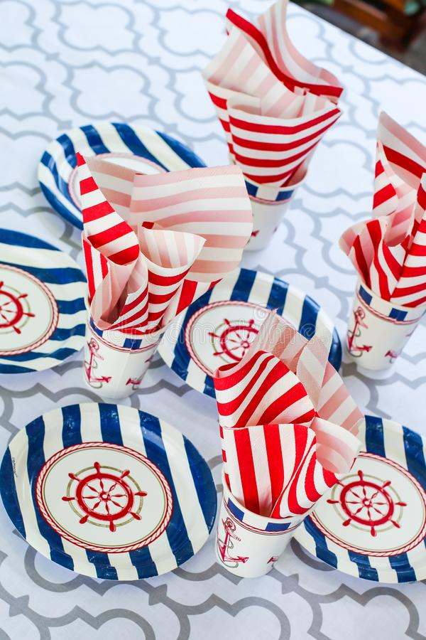 Table serving setting in a marine style. Sea decor. Festive table. Sea theme. Plates, cups and napkins with a sea anchor. And a ship steering wheel stock photo