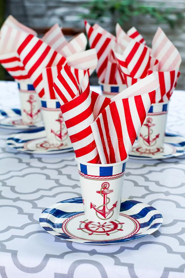 Table serving setting in a marine style. Sea decor. Festive table. Sea theme. Plates, cups and napkins with a sea anchor. And a ship steering wheel royalty free stock photo